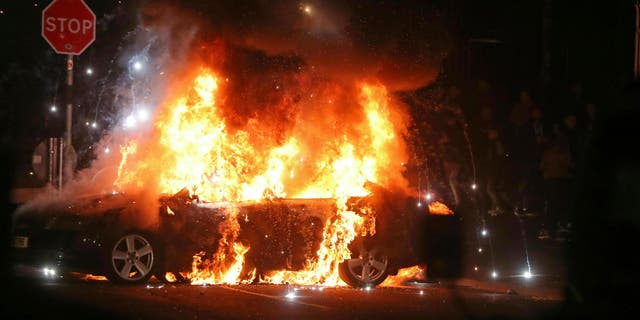 A journalist was shot to death during Northern Ireland rioting, Thursday, April 18, 2019. A car burns after petrol bombs were thrown at police in the Creggan area of Londonderry.