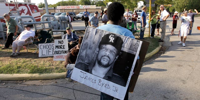FILE - In this Sept. 21, 2011, file photo, Ricky Jason wears a photo of James Byrd Jr. outside the Texas Department of Criminal Justice Huntsville Unit before the execution of Lawrence Russell Brewer in Huntsville, Texas. (Associated Press)
