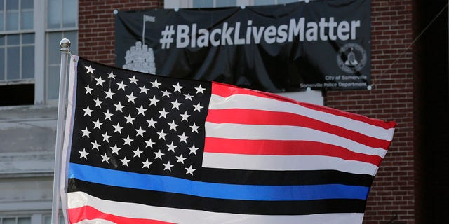 FILE - In this July 28, 2016, file photo, a flag with blue and black stripes in support of law enforcement officers, flies at a protest by police and their supporters outside Somerville City Hall in Somerville, Mass. (Associated Press)