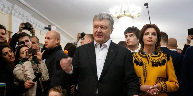 پوترو پوروشنکو، رئیس جمهور اوکراین، در حالی که با رسانه ها صحبت می کند، به همراه همسرش Maryna در کنار ایستادن در ایستگاه رای گیری، در دور دوم انتخابات ریاست جمهوری در کیف، اوکراین، یکشنبه، آوریل 21، 2019. حرکات مهم در انتخابات فساد، اقتصاد و چگونگی پایان دادن به جنگ با شورشیان حمایت شده از روسیه در شرق اوکراین. ()