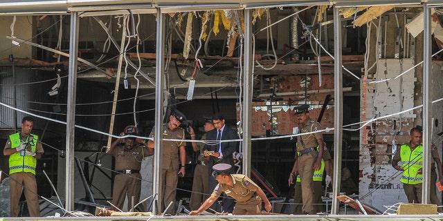 A Sri Lankan police officer inspects a blast site at the Shangri-la Hotel in Colombo, Sri Lanka.