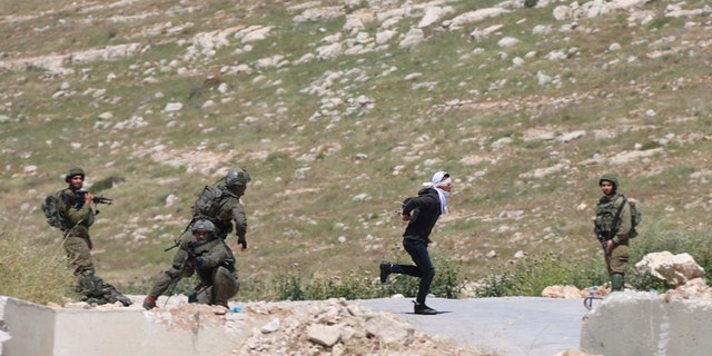 Osama Hajahjeh, 16, bound and blindfolded, runs away from the Israeli soldiers near the village of Tekoa in the West Bank. Hajahjeh said he was shot in the legs by Israeli soldiers last week when he was handcuffed and blindfolded shortly after his arrest. (AP Photo / Mohammad Hmeid)