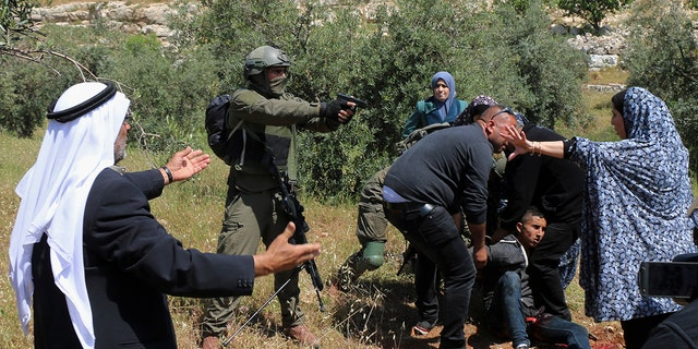 An Israeli soldier points his pistol at a group of Palestinians gathering around a wounded Osama Hajahjeh, 16, near the village of Tekoa, West Bank. (AP Photo/Mustafa Allbadan)