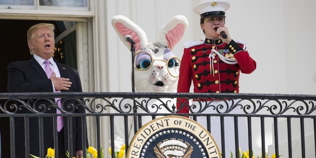 """President Donald Trump, joined by the Easter Bunny, sings the national anthem with a member of the """"The President's Own,"""" United States Marine Band, from the Truman Balcony of the White House in Washington, Monday, April 22, 2019, during the annual White House Easter Egg Roll. (AP Photo/Alex Brandon)"""