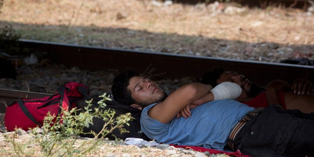 A Central American migrant takes a nap in the shade under a freight train car, during his journey toward the US-Mexico border, in Ixtepec, Oaxaca State, Mexico, Tuesday, April 23, 2019. Whereas in late 2018 and early 2019 Mexican authorities were handing out humanitarian visas and processing asylum requests, they have now largely stopped doing so, instead making migrants wait weeks in the southern town of Mapastepec for visas that never come. (AP Photo/Moises Castillo)