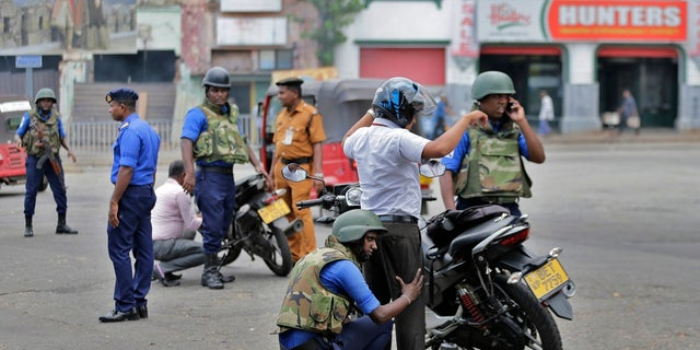 Sri Lankan navy soldiers perform security checks on motorists at a road in Colombo, Sri Lanka on Thursday. (AP Photo/Eranga Jayawardena)
