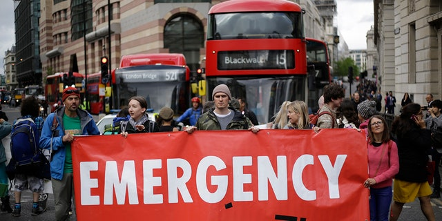 Extinction Rebellion climate change protesters briefly block the road in the City of London, Thursday, April 25, 2019. The non-violent protest group, Extinction Rebellion, is seeking negotiations with the government on its demand to make slowing climate change a top priority.