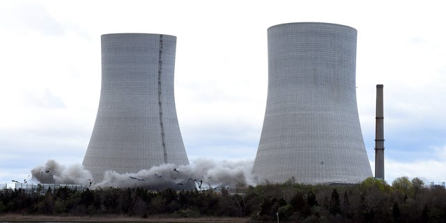The two 500 meter high cooling towers of the former Brayton Point Station begin to collapse after the explosive charge in Somerset starts. Mass.