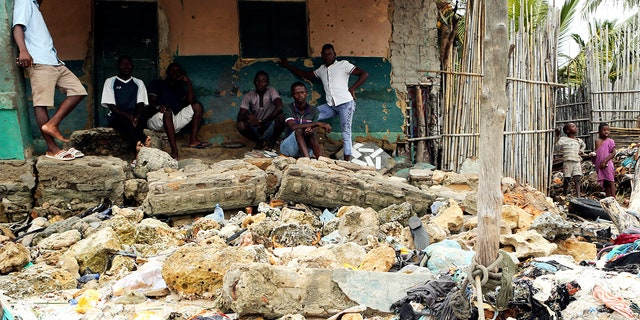 Community members look at rubble and other items washed close to their doorstep when Cyclone Kenneth struck in Pemba city on the northeastern coast of Mozambique, Saturday, April, 27, 2019. (AP Photo/Tsvangirayi Mukwazhi)
