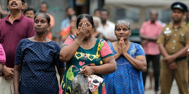Sri Lankan Catholics pray standing on a road as they attend a brief holly service marking the seventh day of the Easter Sunday attacks near the exploded St. Anthony's Church in Colombo, Sri Lanka, Sunday, April 28, 2019. (AP Photo/Eranga Jayawardena)