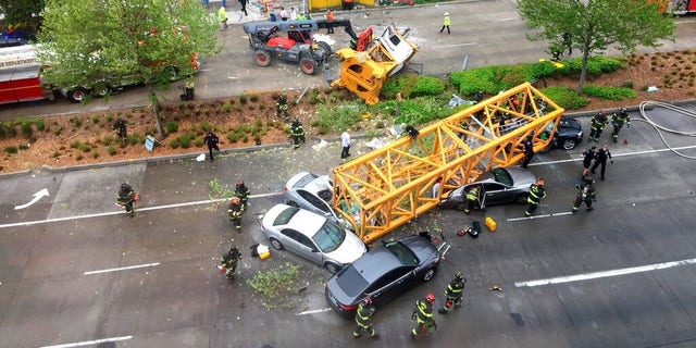 Fire and police crew members work to clear the scene where a construction crane fell from a building on Google's new Seattle campus crashing down onto one of the city's busiest streets and killing multiple people on Saturday.