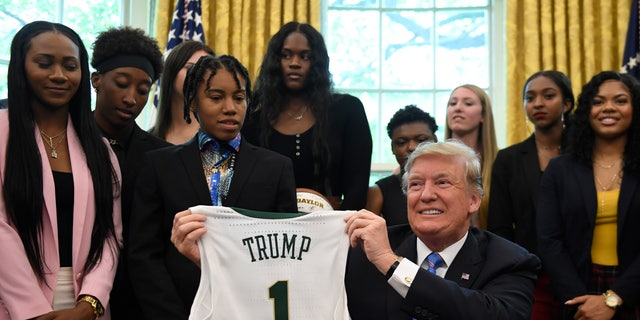 President Donald Trump binds adult a jersey that was presented to him as he welcomed members of a Baylor women's basketball team, who are a 2019 NCAA Division we Women's Basketball National Champions, to a Oval Office of a White House in Washington, Monday, Apr 29, 2019. (AP Photo/Susan Walsh)