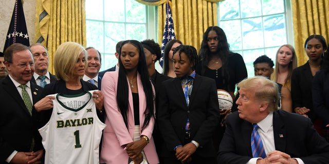 Baylor women's basketball head coach Kim Mulkey, third from left, presents a jersey to President Trump as he welcomed members of the Baylor women's basketball team, who are the 2019 NCAA Division I Women's Basketball National Champions, to the Oval Office of the White House on April 29, 2019. (AP Photo/Susan Walsh)