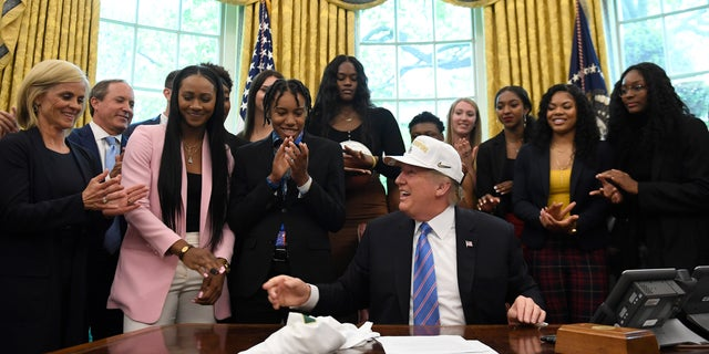 President Donald Trump laughs as he wears a hat that was presented to him as he welcomed members of the Baylor women's basketball team, who are the 2019 NCAA Division I Women's Basketball National Champions, to the Oval Office of the White House in Washington, Monday, April 29, 2019. Baylor women's basketball head coach Kim Mulkey, left, watches. (AP Photo/Susan Walsh)