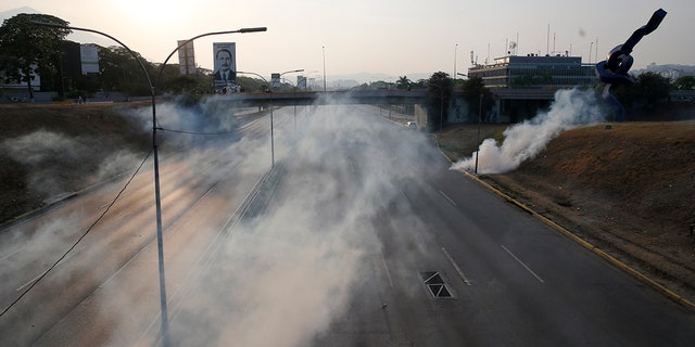 Tear gas covers an empty highway next to La Carlota air base in Caracas, Venezuela, Tuesday, April 30, 2019. Venezuelan opposition leader Juan Guaido appeared in a video with a small contingent of armed soldiers and formerly detained opposition activist Leopoldo Lopez calling for Venezuelans to take to the streets to oust President Nicolas Maduro. (AP Photo/Ariana Cubillos)