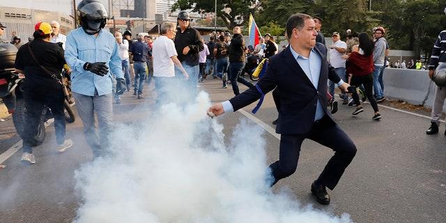 An opponent to Venezuela's President Nicolas Maduro returns a tear gas canister in Caracas, Venezuela, Monday, April 29, 2019. (AP Photo/Ariana Cubillos)