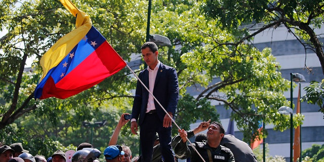 Venezuela's opposition leader and self-proclaimed President Juan Guaido stands above supporters as he addresses them outside La Carlota military air base in Caracas, Venezuela, Tuesday, April 30, 2019. Guaidó has taken to the streets with activist Leopoldo Lopez and a small contingent of heavily armed troops early Tuesday in a bold and risky call for the military to rise up and oust socialist leader Nicolas Maduro. (AP Photo/Fernando Llano)