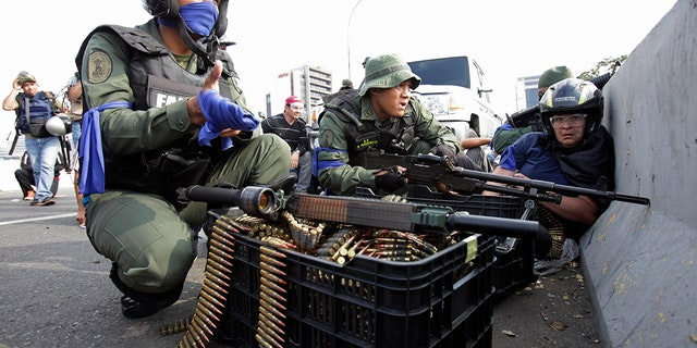 An anti-government protester, right, takes cover amid rebel troops who are rising up against the government of Venezuela's President Nicolas Maduro, on an overpass outside La Carlota military airbase as they confront loyal troops at the base in Caracas, Venezuela, Tuesday, April 30, 2019. (AP Photo/Boris Vergara)