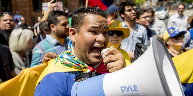 Supporters of opposition leader Juan Guaido supporters yelling chats toward pro-Maduro supporters outside of the Venezuelan Embassy in Washington on Tuesday. (AP Photo/Andrew Harnik)
