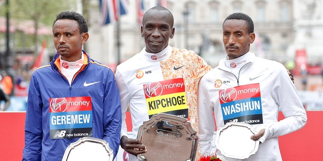 Men's race first place winner Kenya's Eliud Kipchoge, center, poses with second place winner Ethiopia's Mosinet Geremew, left, and third place winner Ethiopia's Mule Wasihun at the 39th London Marathon in London, Sunday, April 28, 2019. (AP Photo/Alastair Grant)
