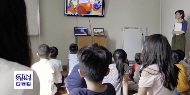 Children at a church in Vietnam watch the children's show, Superbook, a program from the Christian Broadcasting Network, that brings the Bible to animation to millions around the world.
