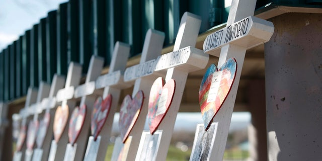Crosses with the names of the victims of the massacre at Columbine High School nearly 20 years ago stand along a picnic site in the park before a vigil at the memorial Friday, April 19, 2019, in Littleton, Colo. (AP Photo/David Zalubowski)