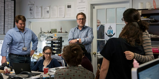 Capital Gazette Editor Rick Hutzell, center, speaks to staffers Monday as the paper won a special Pulitzer Prize citation for its coverage of a shooting that killed five of the paper's staffers. (Ulysses Muoz/The Baltimore Sun via AP)