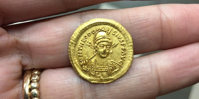 The coin, which bears the image of Byzantine Emperor Theodosius II. (Photograph Nir Distelfeld, Israel Antiquities Authority)