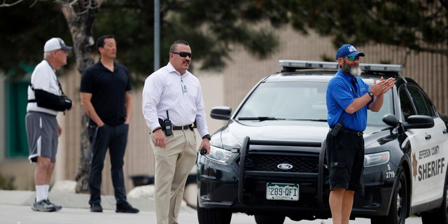School police officers look on as students leave Columbine High School late Tuesday, April 16, 2019, in Littleton, Colo.