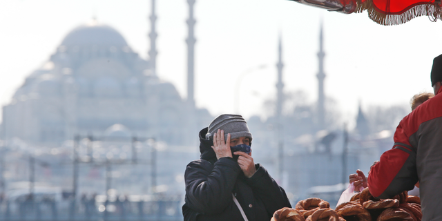 In this Thursday, April 4, 2019 photo, a woman, backdropped by the Suleymaniye mosque, buys simit, a pretzel-like snack, in Istanbul. The mood among opposition supporters in Turkey's biggest city is one of jubilation but also worry - fear that their win in Istanbul's mayoral race could be overturned in a recount taking place after the ruling party challenged the election results. (AP Photo/Lefteris Pitarakis)