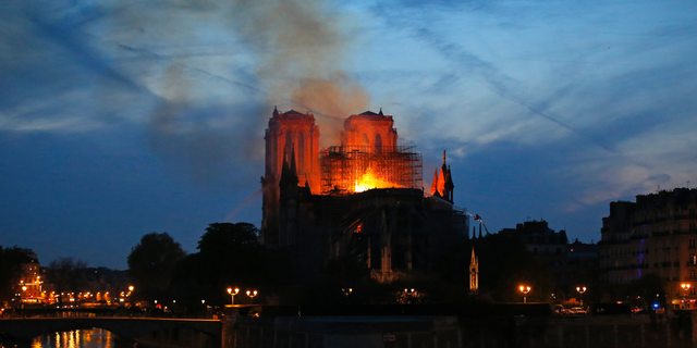 Firefighters tackle the blaze as flames and smoke rises from Notre Dame cathedral as it burns in Paris, Monday, April 15, 2019. Massive plumes of yellow-brown smoke are filling the air above Notre Dame Cathedral and ash is falling on tourists and others around the island that marks the center of Paris.