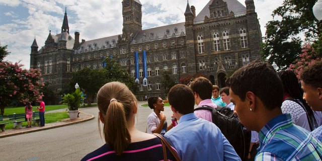 FILE - In this July 10, 2013, file photo, prospective students tour Georgetown University's campus in Washington. Georgetown University students are considering a fee benefiting the descendants of enslaved people sold to pay off the school's debts, an effort that would create one of the first reparations funds at a major U.S. institution. Undergraduates will vote Thursday, April 11, 2019 on a $27.20-per-semester fee that would go toward underprivileged communities where some descendants live. (AP Photo/Jacquelyn Martin, File)
