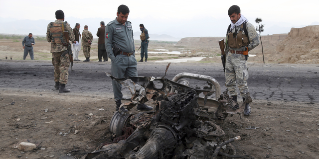 Afghan security forces gather at the site of Monday's suicide attack near the Bagram Air Base, north of Kabul, Afghanistan, Tuesday, April 9, 2019. Three American service members and a U.S. contractor were killed when their convoy hit a roadside bomb on Monday near the main U.S. base in Afghanistan, the U.S. forces said. The Taliban claimed responsibility for the attack. (AP Photo/Rahmat Gul)