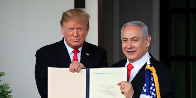 In this March 25, 2019 photo, Israeli Prime Minister Benjamin Netanyahu and President Donald Trump hold up the signed proclamation recognizing Israel's sovereignty over the Golan Heights at the White House in Washington. (AP Photo/Manuel Balce Ceneta, File)