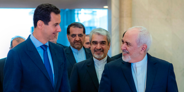 This photo released on the official Facebook page of Syrian Presidency shows Syrian President Bashar Assad, left, speaking with Iranian Foreign Minister Mohammad Javad Zarif, right, in Damascus, Syria, Tuesday, April 16, 2019. (Syrian Presidency Facebook page via AP)