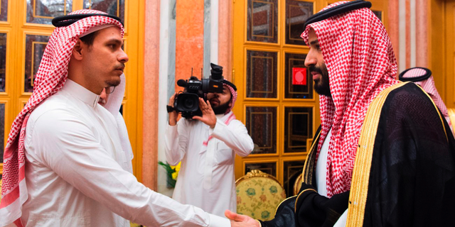 """FILE - In this Oct. 23, 2018, file photo released by Saudi Press Agency, SPA, Saudi Crown Prince Mohammed bin Salman, right, shakes hands with Salah Khashoggi, a son, of Jamal Khashoggi, in Riyadh, Saudi Arabia. The son of slain Washington Post columnist Jamal Khashoggi says no settlement discussions have taken place and suggested that financial compensation to the family did not amount to an admission of guilt by Saudi rulers. Salah Khashoggi described King Salman and Crown Prince Mohammed bin Salman as """"guardians to all Saudis."""" (Saudi Press Agency via AP, File)"""