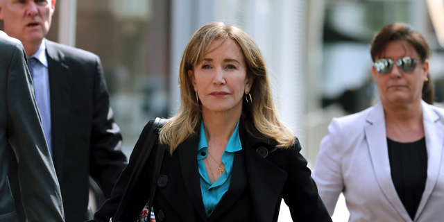 This April 3, 2019 file photo shows actress Felicity Huffman arriving at federal court in Boston to face charges in a nationwide college admissions bribery scandal. Huffman is facing a prison sentence after agreeing Monday to plead guilty to one count of conspiracy and fraud for paying a consultant $15,000 disguised as a charitable donation to boost her daughter's SAT score. Prosecutors are seeking four to 10 months of confinement, and experts differ on whether the plea, and Huffman's subsequent apology taking full responsibility for her actions, will lead to a career rebound or retreat. (AP Photo/Charles Krupa, File)