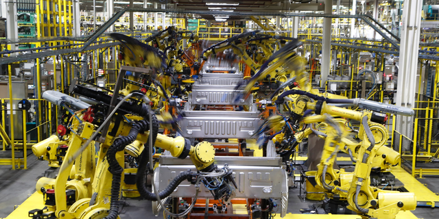 FILE- In this Sept. 27, 2018, file photo robots weld the bed of a 2018 Ford F-150 truck on the assembly line at the Ford Rouge assembly plant in Dearborn, Mich. On Monday, April 1, the Institute for Supply Management, a trade group of purchasing managers, issues its index of manufacturing activity for March.  (AP Photo/Carlos Osorio, File)