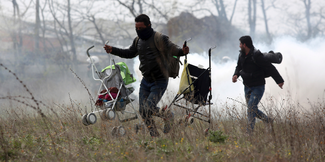 A man holding two baby strollers runs to avoid tear gas thrown by riot police during clashes outside a refugee camp in the village of Diavata, west of Thessaloniki, northern Greece, Friday, April 5, 2019. Clashes broke out Thursday between migrants and Greek police outside a camp in northern Greece, where hundreds gathered in the hope of reviving a route that saw hundreds of thousands enter more prosperous countries in Europe. (AP Photo/Giannis Papanikos)