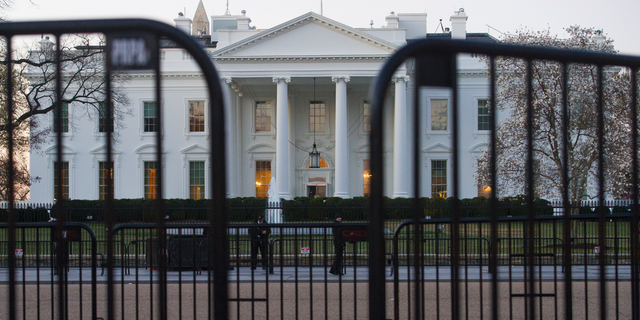 """In this March 24, 2019 photo, The White House is seen behind security barriers in Washington. A White House official turned whistleblower says dozens of people in President Donald Trump's administration were granted access to classified information despite """"disqualifying issues"""" in their backgrounds including concerns about foreign influence, drug use and criminal conduct.  (AP Photo/Cliff Owen)"""