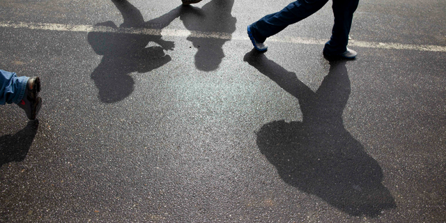 FILE - In this Aug. 14, 2012 file photo, Honduran migrants walk along a road after being deported by bus from Mexico to Corinto, Honduras, near the border with Guatemala. On Sunday, April 14, 2019, Mexican immigration officials said they have sent a group of just over 200 migrants back to Honduras, most of them families traveling with underage children, and that they were flown from the southeastern Mexican state of Veracruz to San Pedro Sula. (AP Photo/Esteban Felix, File)