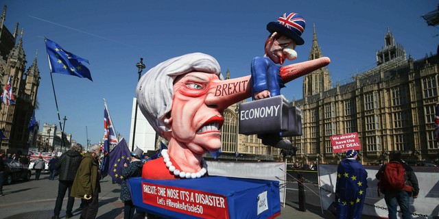 Protesters against Brexit with a picture of British Prime Minister Theresa May near College Green in the Houses of Parliament in London on Monday, April 1, 2019. (Jonathan Brady / PA via AP)