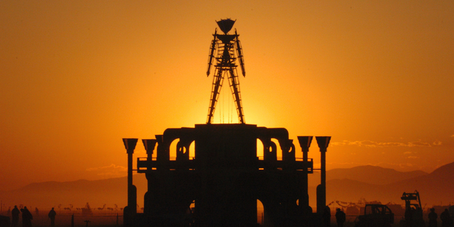 FILE - In this Sept. 2, 2006 file photo, The Man, a stick figured symbol of the Burning Man art festival, is silhouetted against a morning sunrise in Nevada's Black Rock Desert. Burning Man organizers say the U.S. government wants to place unreasonable conditions on a proposal to expand the counter-culture festival's capacity to 100,000, including more security searches and hardened barriers around the perimeter that the agency says would reduce vulnerability to terrorism. (AP Photo/Ron Lewis, File)