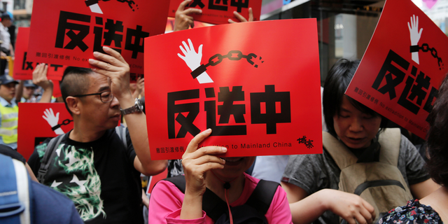 """People raise placards reading """" Against Extradition law"""" as thousands of protesters march along a downtown street against the extradition law in Hong Kong Sunday, April 28, 2019. (AP Photo/Vincent Yu)"""