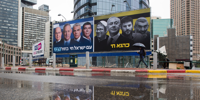 """FILE - In this Saturday, March 16, 2019 file photo, an Ultra-Orthodox Jewish man looks at an elections billboards of the Blue and White party leaders, from left to right, Moshe Yaalon, Benny Gantz, Yair Lapid and Gabi Ashkenazi, alongside a panel on the right showing Prime Minister Benjamin Netanyahu flanked by extreme right politicians, from the left, Itamar Ben Gvir, Bezalel Smotrich and Michael Ben Ari in Ramat Gan, Israel, In a charged campaign that has been heavy on insults and short on substance, Israel's conflict with the Palestinians has been notably absent from the discourse. Hebrew reads on the left billboard """"The nation of Israel lives"""" and on the right billboard """"Kahana Lives"""" in a reference to a banned ultranationalist party. (AP Photo/Oded Balilty, File)"""
