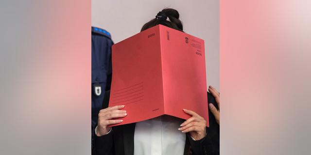 جنیفر، 27 ساله، در حالی که در دادگاه در مونیخ، جنوب آلمان، سه شنبه، 9 آوریل 2019، به چهره او می رسد، زن را متهم به اجازه دادن به یک دختر 5 ساله او و شوهرش یک برده در قلمرو حکومت اسلامی در عراق از تشنگی میمیرد. (Peter Kneffel / dpa via AP)