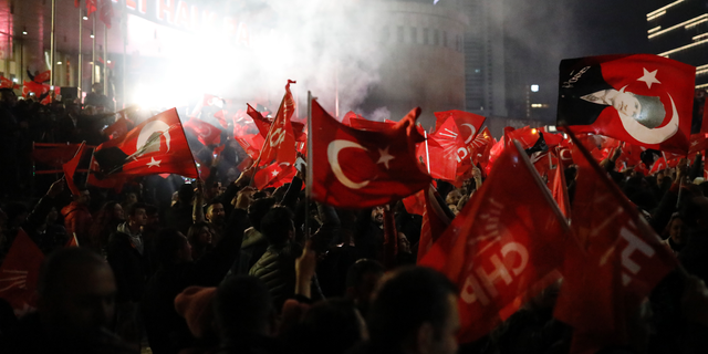 Supporters of the Republican People's Party, CHP, wave Turkish flags, and one with a portrait of Kemal Ataturk, right, as they celebrate after preliminary results of the local elections were announced in Ankara, Turkey, early Monday, April 1, 2019.