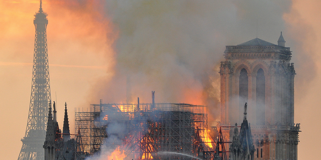 In this image made available on Tuesday April 16, 2019 flames and smoke rise from the blaze after the spire toppled over on Notre Dame cathedral in Paris, Monday, April 15, 2019.