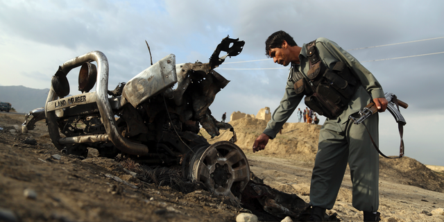 An Afghan security force check the site a day after an an attack near the Bagram Air Base, north of Kabul, Afghanistan, Tuesday, April 9, 2019. Three American service members and a U.S. contractor were killed when their convoy hit the roadside bomb on Monday near the main U.S. base in Afghanistan, the U.S. forces said. The Taliban claimed responsibility for the attack. (AP Photo/Rahmat Gul)