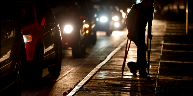 In this March 29, 2019 file photo, a man on crutches is illuminated by headlights of oncoming traffic, in Caracas, Venezuela. Venezuelans are struggling to understand the Sunday, March 31, 2019 announcement that the nation's electricity is being rationed to combat daily blackouts. (AP Photo/Natacha Pisarenko, File)